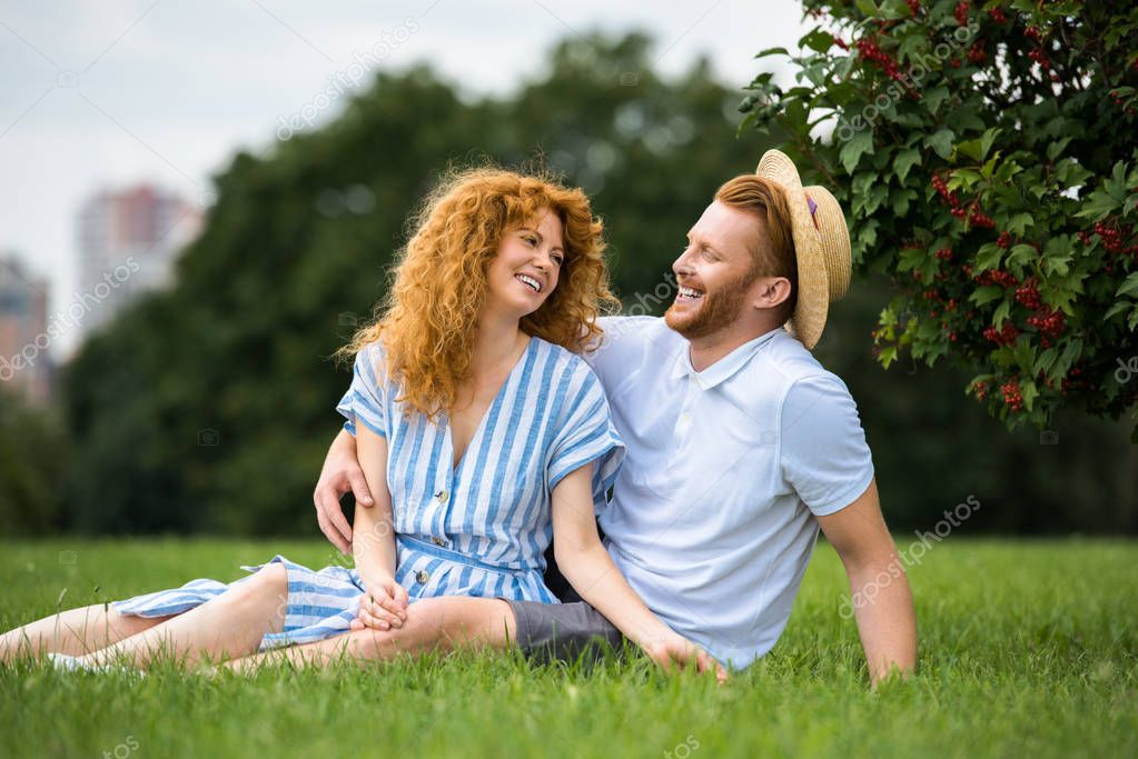 happy redhead man sitting in girlfriends straw hat while his girlfriend sitting near on grass in park