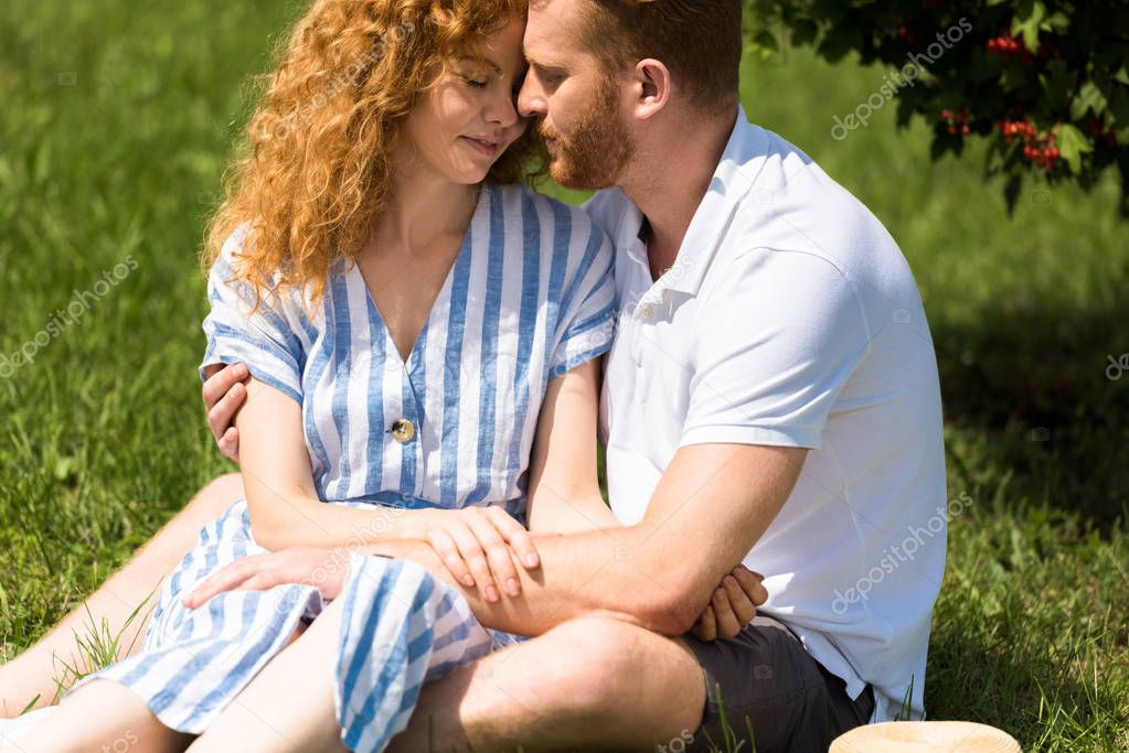 redhead couple with closed eyes embracing each other on grass in park