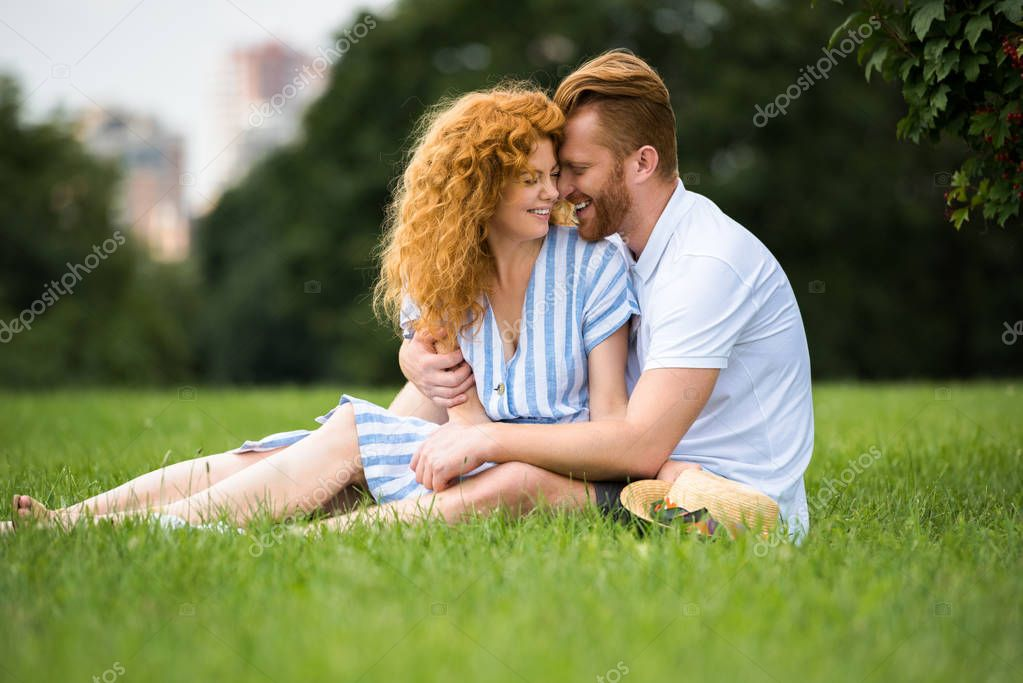 smiling redhead couple embracing and sitting on grass in park