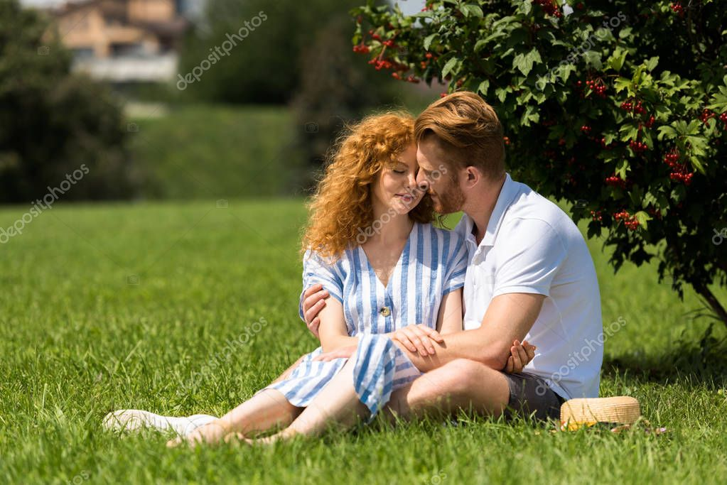 redhead couple sitting on grass in park