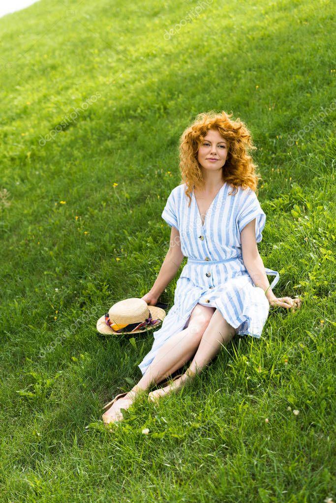 beautiful redhead attractive woman sitting on grass