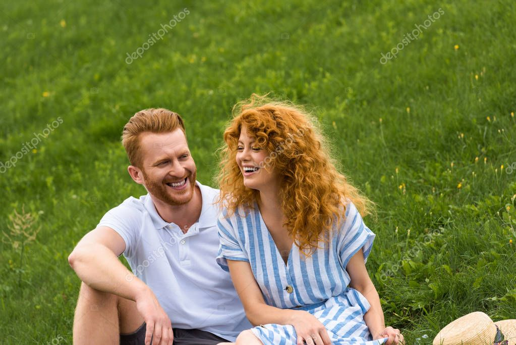 laughing redhead woman sitting with boyfriend on grassy meadow