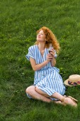 Photo smiling redhead woman sitting on grassy meadow with soda
