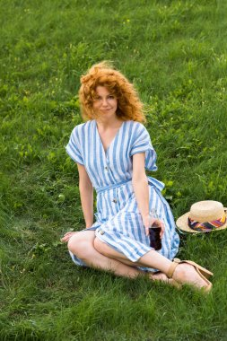 attractive redhead woman sitting on grass with soda