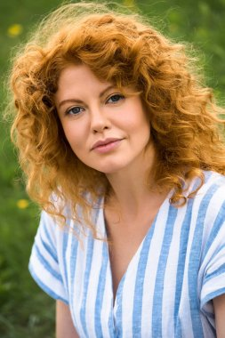 portrait of attractive redhead woman looking at camera outdoors