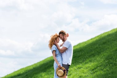side view of happy redhead couple standing face to face on green hill