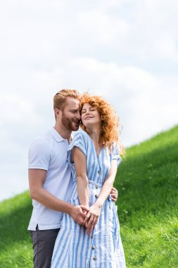 happy redhead man embracing girlfriend from behind on grassy hill