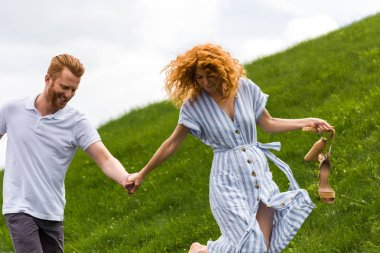 happy redhead woman holding shoes in hand and walking with boyfriend on grassy hill