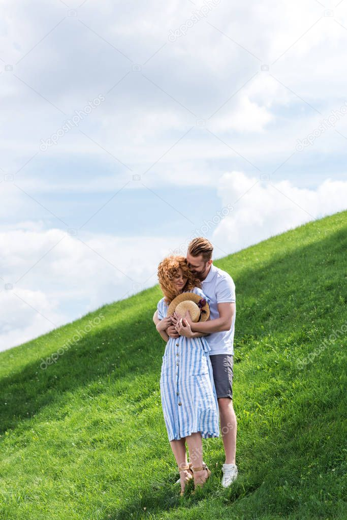 smiling redhead man hugging girlfriend from behind on green hill