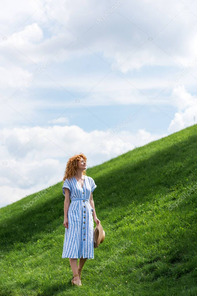 smiling beautiful redhead woman in straw hat on grassy hill
