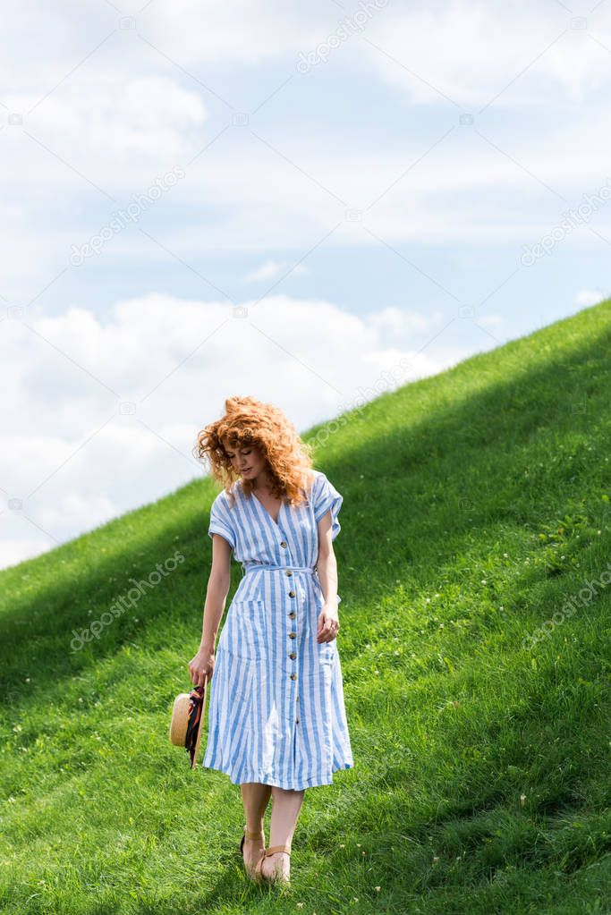 redhead woman posing with straw hat on grassy hill against blue sky