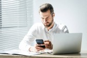 handsome fashionable businessman using smartphone at workplace with laptop and documents