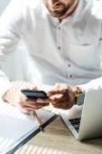 oříznutý pohled podnikatel pomocí smartphone na pracovišti s notebookem a papírování