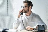 Fotografia barbuto delluomo daffari comunica sul telefono rotativo sul posto di lavoro con larma