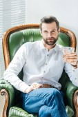 handsome man holding glass of whiskey and sitting in green armchair near window