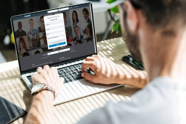 partial view of man using laptop with linkedin website on screen