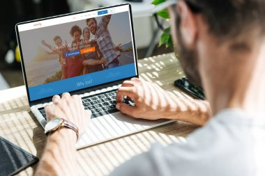 Cropped view of man using laptop with couchsurfing website on screen stock vector