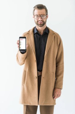fashionable man in brown coat presenting smartphone with apple music appliance, isolated on white
