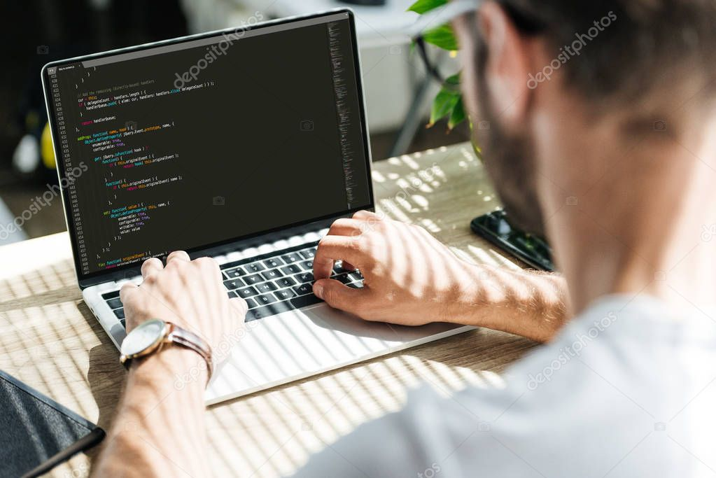 back view of man using laptop with html code on screen