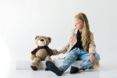 Photo full length view of beautiful stylish kid sitting and looking at teddy bear on white