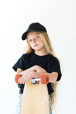 beautiful child in black cap and t-shirt standing with skateboard and looking at camera isolated on white