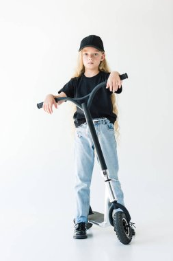 full length view of kid with long curly hair standing with scooter and looking at camera isolated on white