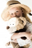 Photo beautiful child in straw hat hugging teddy bear and looking at camera on white