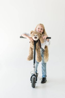 Beautiful kid with long curly hair standing with scooter and teddy bear, smiling at camera on white stock vector