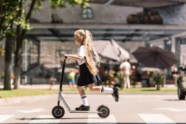 side view of cute little child with long curly hair riding scooter on street