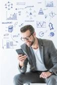 Fotografie stilvolle Seo-Entwickler im grauen Anzug mit Smartphone, isoliert auf weiss mit Erfolg icons
