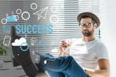 Fotografie Stylový vousatý podnikatel v klobouku drží sklenku whisky, úspěch ikonami