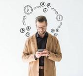 Fotografie pohledný podnikatel v hnědém kabátě pomocí smartphone, izolované na bílém s ikonami čas a peníze