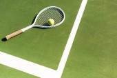 zblízka pohled tenisovou raketu a míček leží na zelený tenisový kurt