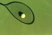 pohled shora tenisák a tenisové rakety stín na zelený tenisový kurt