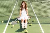 mladí módní tenista v bílé sportovní a sluneční brýle sedí u netu s tenis zařízení kolem na tenisový kurt