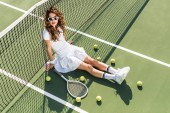 Photo high angle view of young stylish tennis player in white sportswear and sunglasses sitting at net with tennis equipment around on tennis court