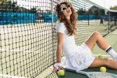 boční pohled na mladé stylové tenista v bílé sportovní a sluneční brýle sedí u netu s tenis zařízení kolem na tenisový kurt