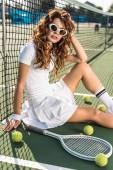 boční pohled na módní tenista v sluneční brýle sedí u netu s tenis zařízení kolem na tenisový kurt