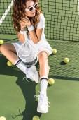 Mladá krásná sportovkyně v sluneční brýle s tenisovou raketu sedí na tenisový kurt na tenis sítě