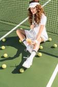 Módní sportovkyně v bílém oblečení s tenisovou raketu s selfie na smartphone na net na tenisový kurt