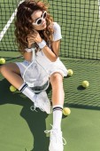 Photo young beautiful sportswoman in sunglasses with tennis racket sitting at tennis net on tennis court