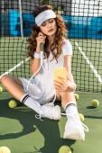 Stylový sportovkyně v bílém oblečení s tenisovou raketu s selfie na smartphone na net na tenisový kurt