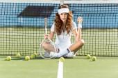 krásná tenistka raketou sedí poblíž tenisové sítě na kurtu s tenisovými míčky a okolí