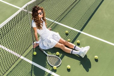 high angle view of young beautiful tennis player in white sportswear and sunglasses sitting at net with tennis equipment around on tennis court