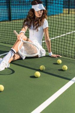 Beautiful tennis player in white tennis uniform with racket sitting near tennis net on court with tennis balls around stock vector