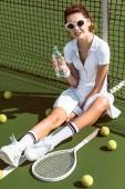 krásná tenistka v jednotné bílé tenis a sluneční brýle s lahví vody spočívající na soudu s pálky a míčky