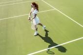 a fiatal, vonzó nő fehér tenisz egységes teniszezni a bíróság oldalnézete