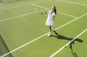 Fotografie boční pohled na mladé atraktivní ženy v bílém tenisu jednotné hrát tenis na kurtu