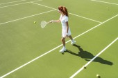 Photo side view of young attractive woman in white tennis uniform playing tennis on court