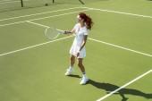 mladá tenistka v sluneční brýle hrát tenis na kurtu
